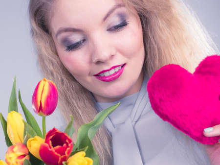 International womens or valentines day. Attractive grateful woman blonde hair holding tulips bunch and red heart sign. On grey