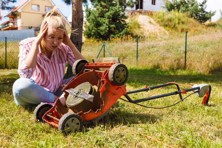 Gardening. Female person gardener mowing green lawn with lawnmower, having problem with broken mower Stockfoto