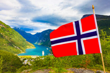 Norwegian flag and beautiful view over Geirangerfjorden from Flydalsjuvet viewing point. Tourist attraction. Tourism vacation and travel. Stok Fotoğraf