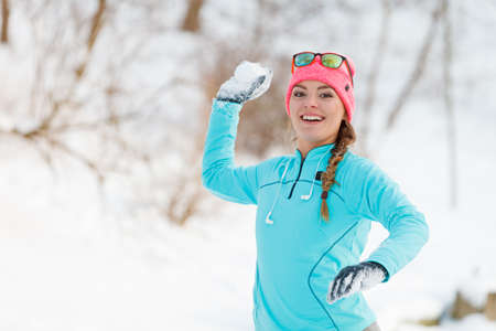 Girl playing games in snow. Young woman tossing snowballs. Health nature fashion fitness concept.