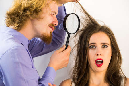 Man looking at woman hair using magnifying glass. Female looking unhappy having some haircare problems, split ends or lice