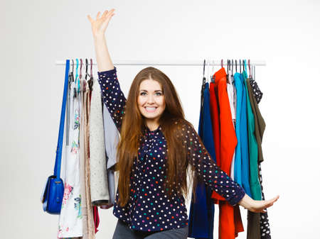 Happy young woman during shopping time picking clothes for perfect fashionable outfit.