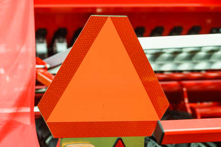 Detail industry machine with reflective slow moving vehicle warning sign in triangle shape