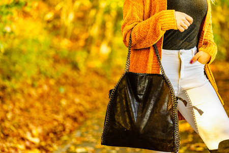 Unrecognizable woman wearing long orange warm cardigan sweater. Autumnal fashion, autumn season styled outfits. Female having a walk in park