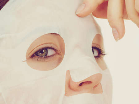Woman applying sheet mask on her face. Girl taking care of skin complexion. Beauty treatment. Skincare. Stock Photo