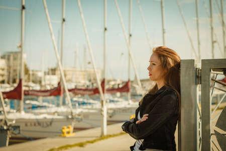 Nostalgic woman walking around jetty pier wearing black jeans jacket. Female fashion model during spring weather, having long brown hair wind tousled. Stock Photo