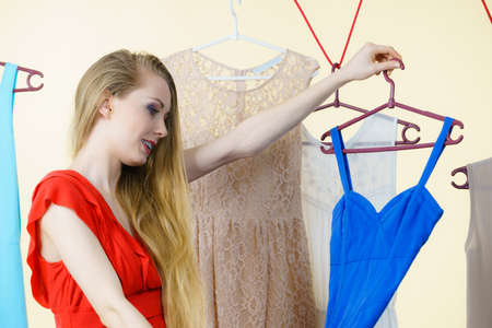 Young blonde long hair woman in clothes in shop or wardrobe choosing summer outfit, dresses hanging on clothing hangers. Sale shopping fashion and style concept Фото со стока - 119051679