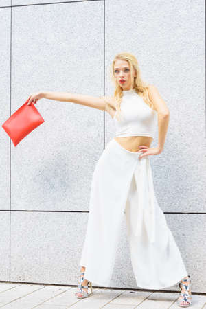Attractive fashionable woman in trendy urban outfit white crop top trousers culottes and high heels shoes. Female model holding red handbag.