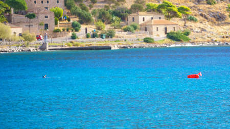 Blue aqua sea water with buoys next to coastline during sunny summertime weather.
