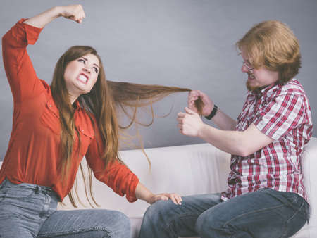 Teen brother and sister having horrible fight, man pulling woman hair. Friendship and family problems concept.