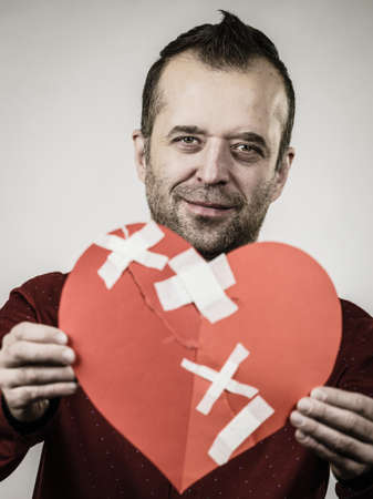 Healed love. Valentines Day concept. Adult smiling man holding big red heart with plaster. Male healing relationship. Banco de Imagens - 119092711