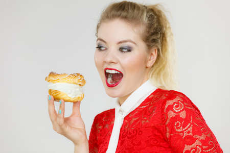 Sweet food and happiness concept. Funny joyful blonde woman holding yummy choux puff cake with whipped cream, taking huge bite, excited face expression. On gray