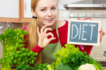 Young woman in kitchen having many green vegetables presenting board with diet sign.