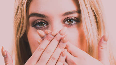 Close up of young blonde woman showing silence gesture hiding her mouth being hands. Stockfoto