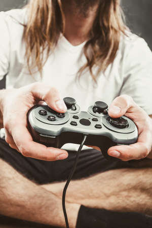 Playing games concept. Part body man with joystick play game on console playstation. Male hands holding grey pad. Stock Photo