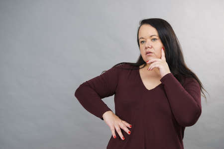 Thinking adult woman, plus size female gesturing with hands seeking for solution, having contemplating face expression.