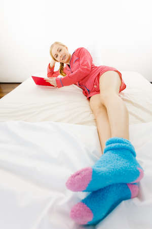 Girl lying in bed reading book. Young blonde female wearing red dotted pajamas blue warm socks relaxing at home on mattress.