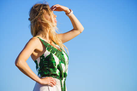 Beautiful fashion model against blue clear sky looking in distance gesturing with hands, sunlight.