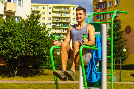 Young handsome man working out in outdoor gym. Sporty guy flexing his muscles doing sit ups on machine. Staying fit and healthy.