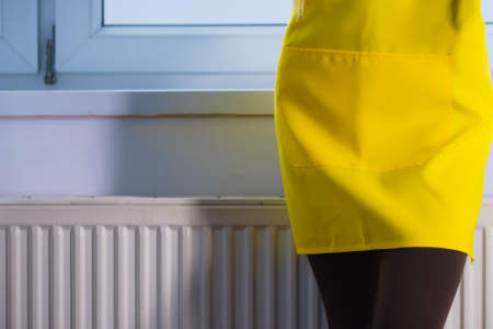 Unrecognizable person standing next to warmer heater wearing yellow apron. Household duties concept