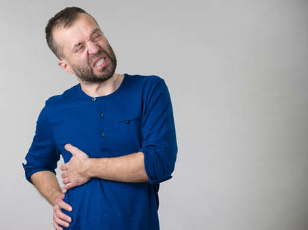 Adult guy suffering from stomach or ribs pain ache. Health problems and issues concept. Stock Photo