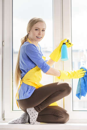Young woman in yellow gloves cleaning window pane at home with rag and spray detergent. Cleaning concept