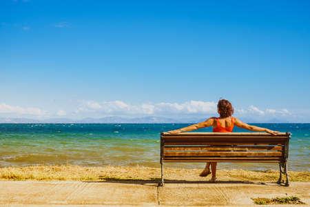 Reisefreiheitskonzept. Touristische reife Frau, die auf Bank am Seeufer sitzt und Sommerferien genießt, Ozean betrachtet Standard-Bild