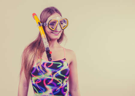 Woman wearing swimsuit with snorkeling mask having fun studio shot, Happy joyful girl dreaming about active summer vacation. Snorkeling swimming concept