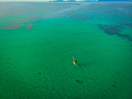 Aerial view of surfer in clear water beach, Lofoten Norway Imagens