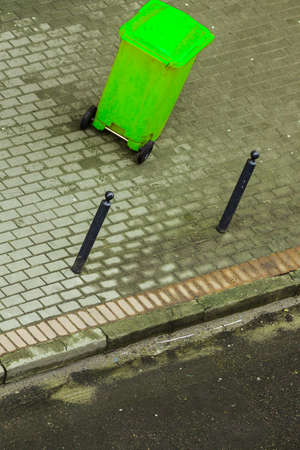 Plastic green wheely bin in the street outside waiting for garbage truck. Top view