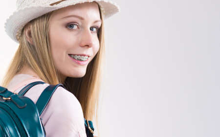 Happy young blonde teenage girl going to school or college wearing backpack. Stock Photo
