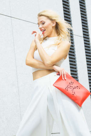 Attractive fashionable woman in trendy urban outfit white crop top trousers culottes posing outdoor. Female model holding red handbag. Stock Photo