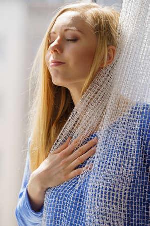 Glückliche Frau mit langen blonden Haaren, die auf Fensterbank sitzen und sich entspannen, meditieren oder denken, weißen Spitzenvorhang haltend.