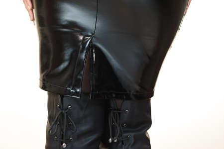 Femme méconnaissable vêtue d'une tenue toute noire, jupe moulante en latex de cuir noir montrant les courbes de ses hanches.