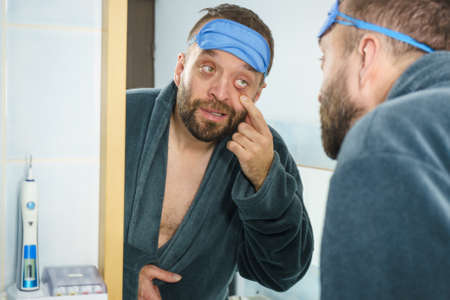 Funny adult man wearing eyemask on forhead having troubles with waking up. Standing in front of mirror looking at his dark circles under eyes, being tired and sleepy. 写真素材