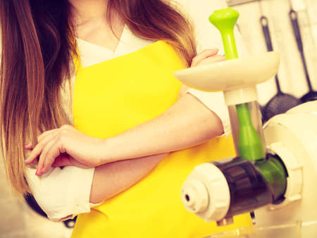 Woman housewife in kitchen with juicer machine preparing to make fresh juice, Healthy eating, cooking, dieting and people concept.