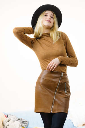 Beautiful pretty woman wearing brown suede outfit and black sun hat. Female having fashionable outfit.