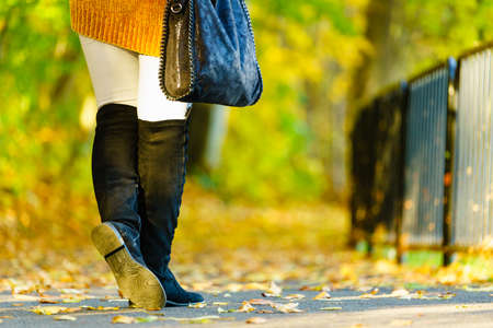 Woman presenting black suede high knee black boots holding big hand bag. Autumnal fashion, autumn season styled outfits. Female having a walk in park