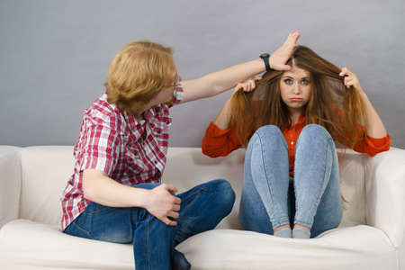 Teenage brother annoying his sister. Woman being sad, man playing with her in rude way.