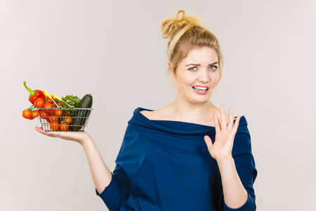 Adult woman do not like to eat vegetables, healthy food, vegetarian products. Female holding small shopping basket with green red vegetables, negative displeased face expression, on grey Foto de archivo - 120868749