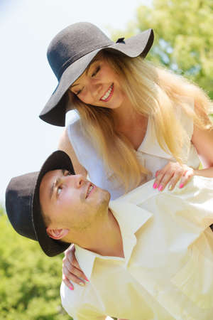 Love, romantic walks concept. Man and blonde woman in sun hats having romantic date in park, happy being together.