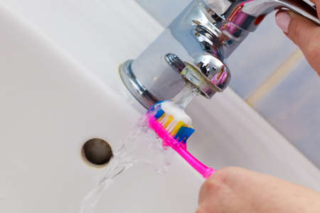Dental care. Woman hands is holding toothbrush with toothpaste in bathroom, sink and running faucet in background