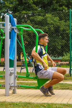 Young handsome man working out in outdoor gym. Sporty guy flexing his muscles on machine. Staying fit and healthy.
