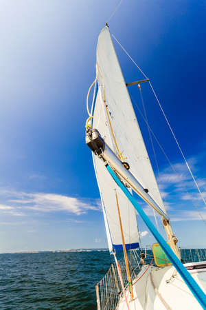 Yachting on sail boat during sunny summer weather on calm blue sea water. Sporty transportation conept.