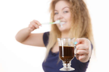 Happy woman holding toothbrush and coffee going to brush her teeth after hot drink. Discoloration prevention.