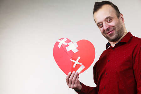 Healed love. Valentines Day concept. Adult smiling man holding big red heart fixed with plaster bandage. Male healing relationship. Stock fotó - 121268313