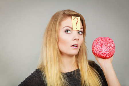 Intellectual expressions, being focused concept. Closeup of attractive woman thinking face expression holding brain having question mark on head 免版税图像