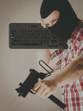 Crazy hacker man. Unrecognizable guy wearing black balaclava holding computer keyboard and gun. Hate speech on the internet.