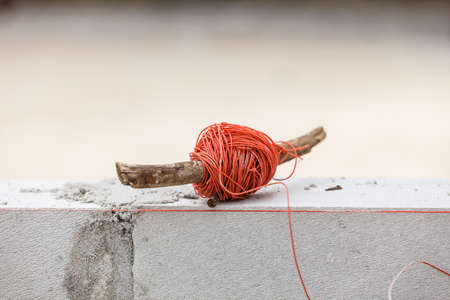 String net on wooden stick. Tool to help you set straight distances, spirit level.