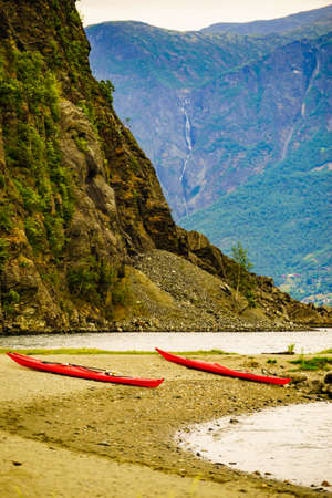 Kayaks on fjord shore in norwegian tourist destination Flam village. Travel, holidays and active lifestyle. Stock Photo